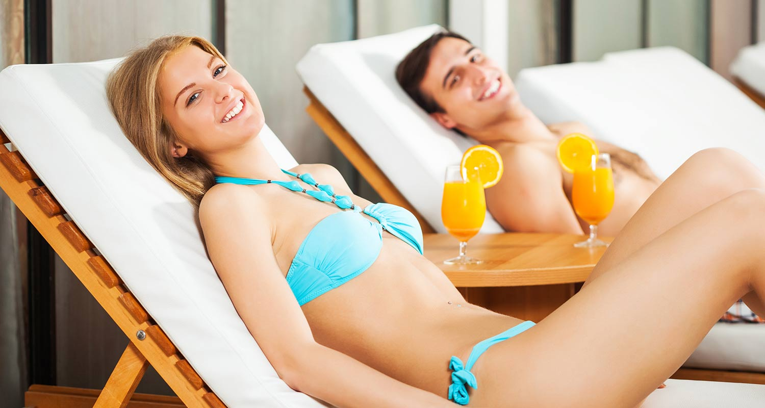 Couple in the relaxation room of the spa with a fruit cocktail