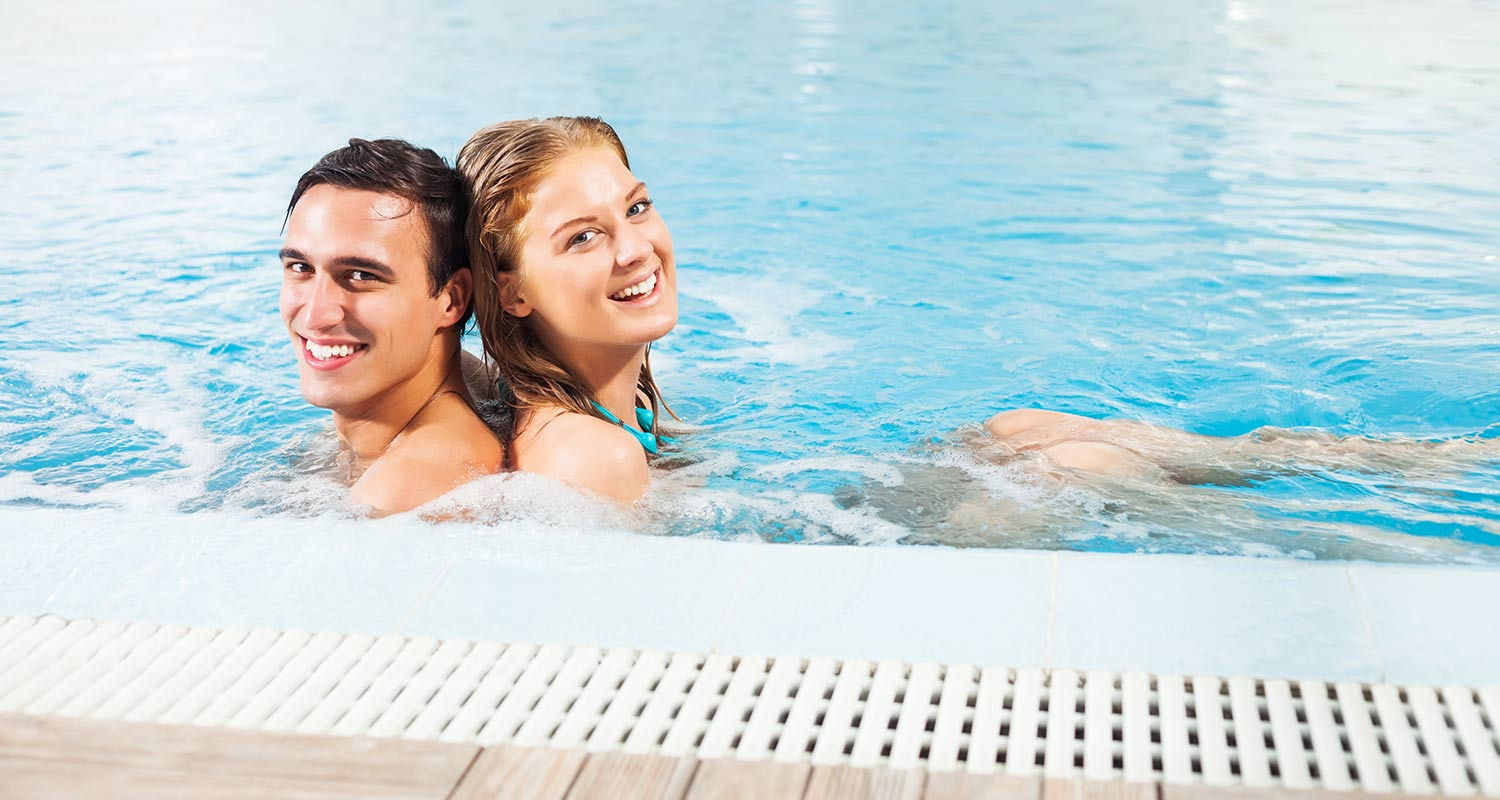 Smiling couple at indoor pool of Sporthotel Rasen