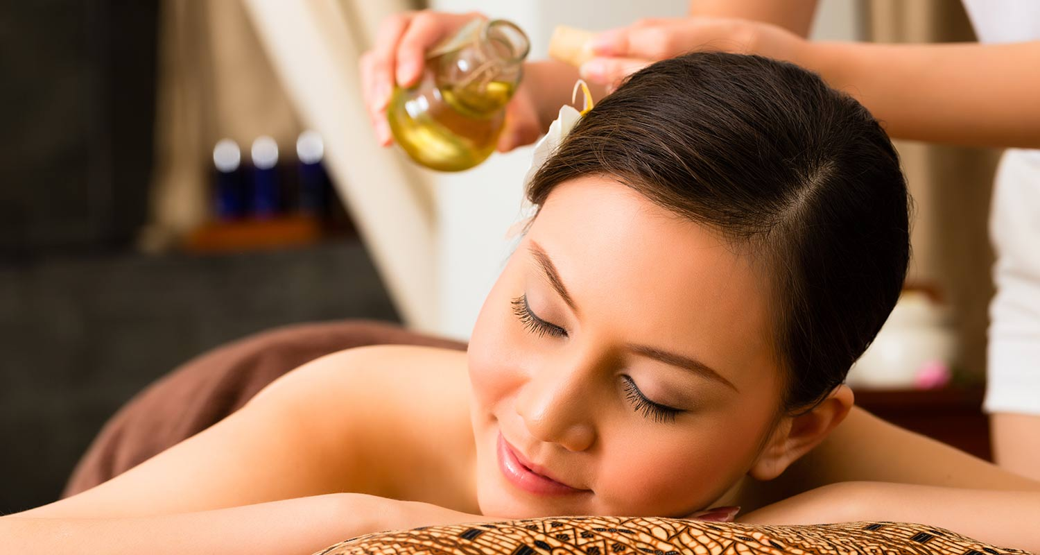 Woman with eyes closed enjoying an oil massage