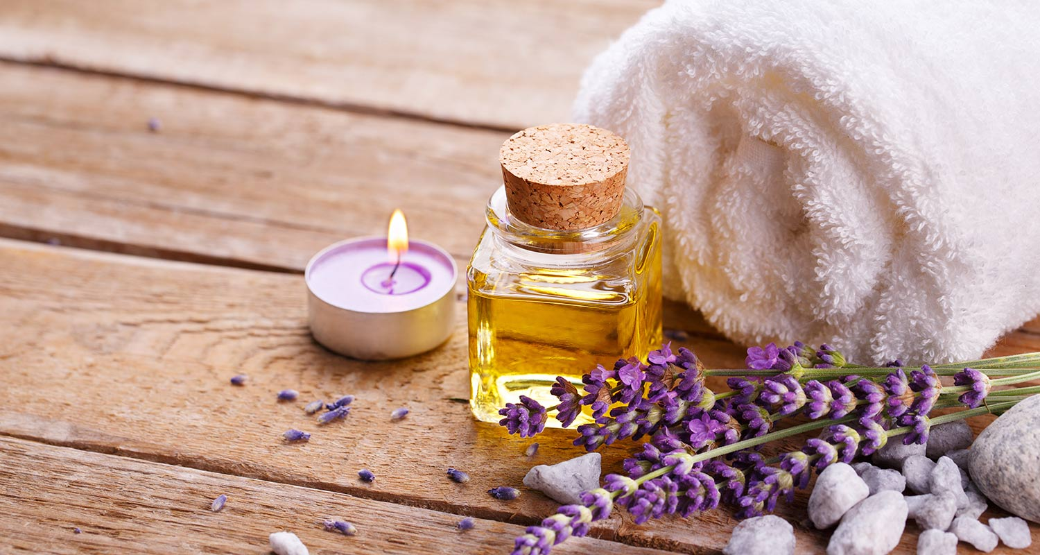 Wooden floor with massage oil, lavendar, towel and candle