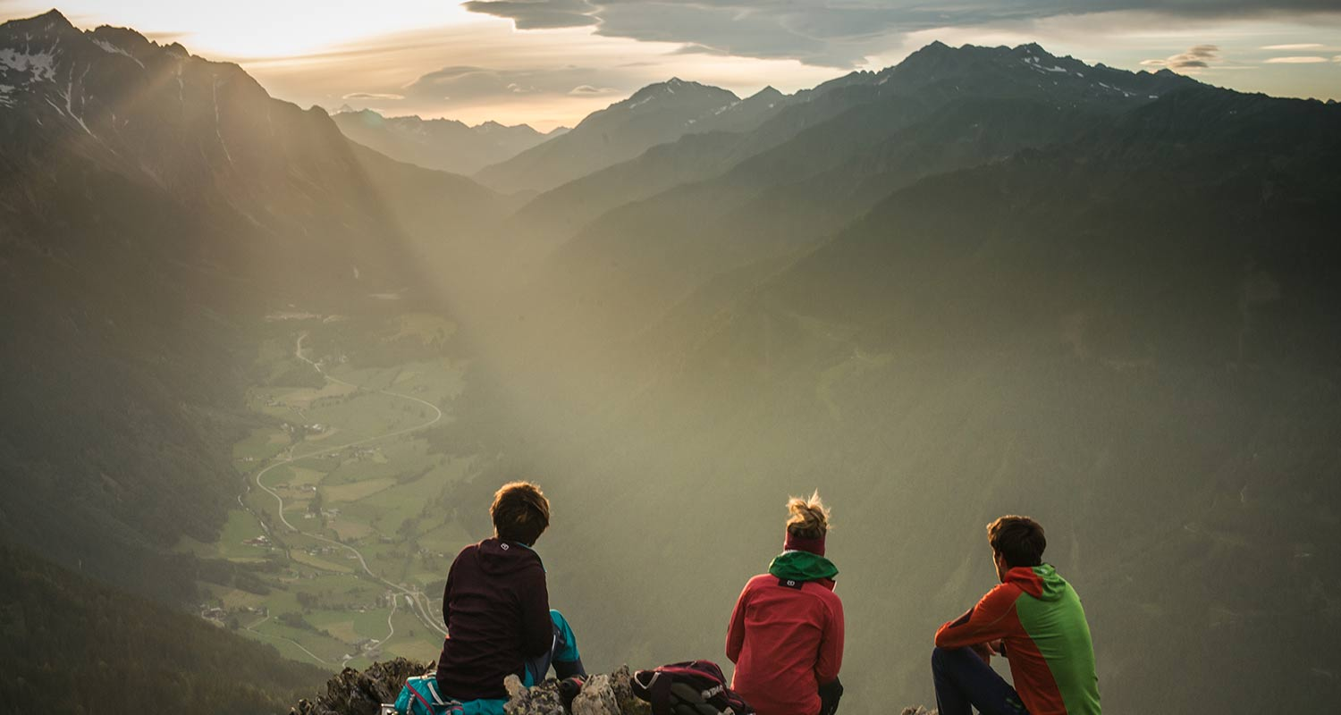 Three people enjoying the view at sunrise from a mountain top in Pustertal