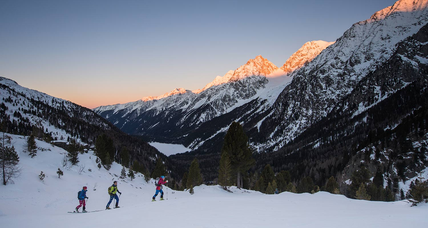 Group of cross-country skiers at sunset in a snow-covered landscape