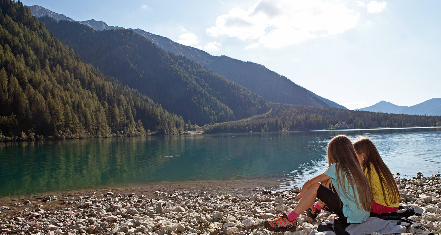Two girls sitting on the lake shore with mountains at the back