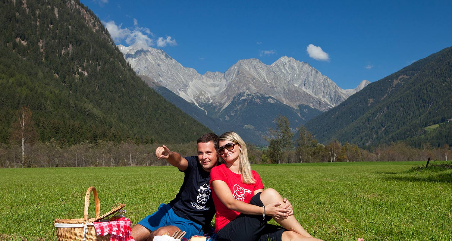 Couple having a picknick on a moutain meadow on a beautiful summer day