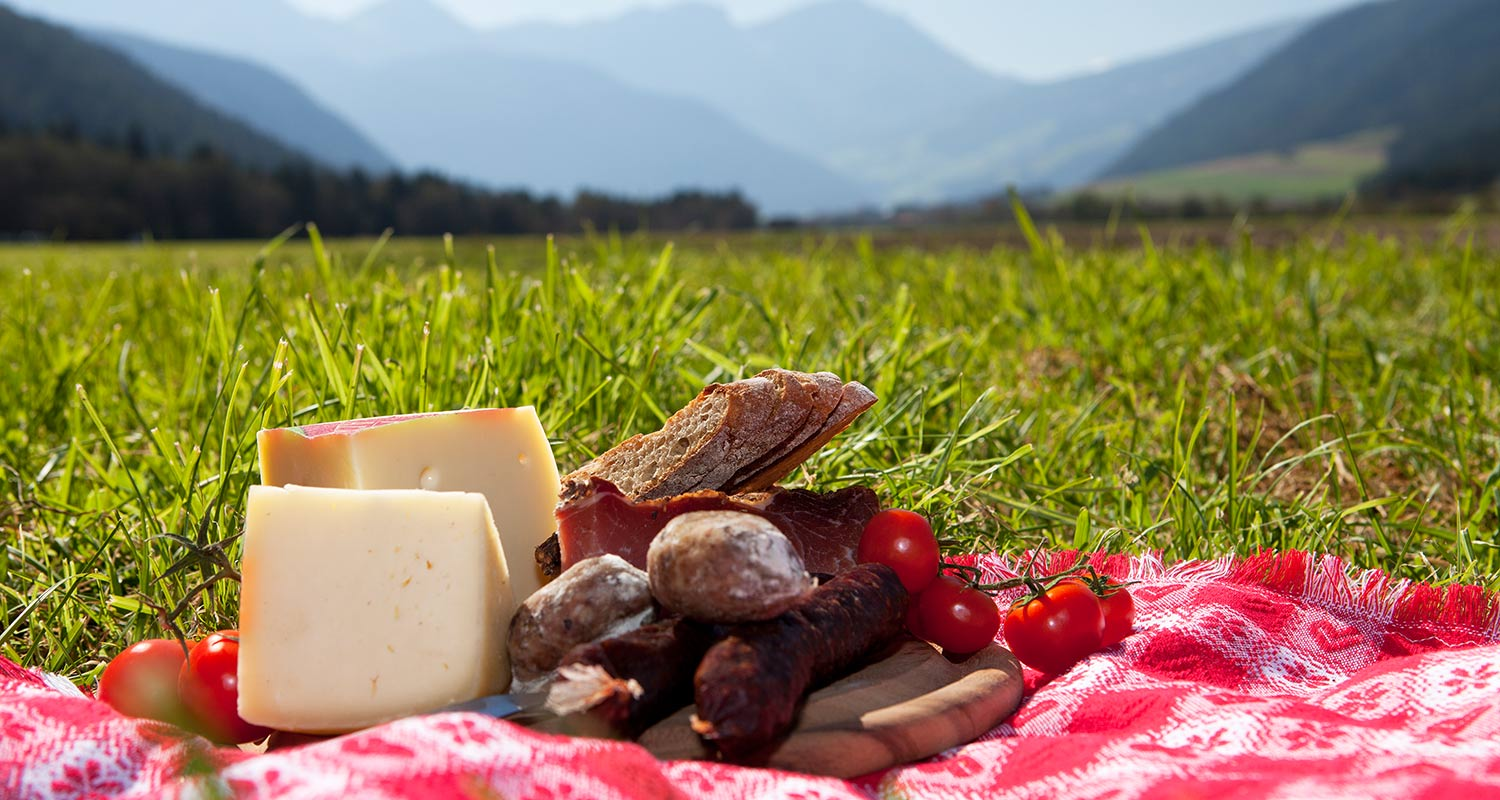 Close-up with open picknick basket with cheese, cured meat and cherry tomatoes
