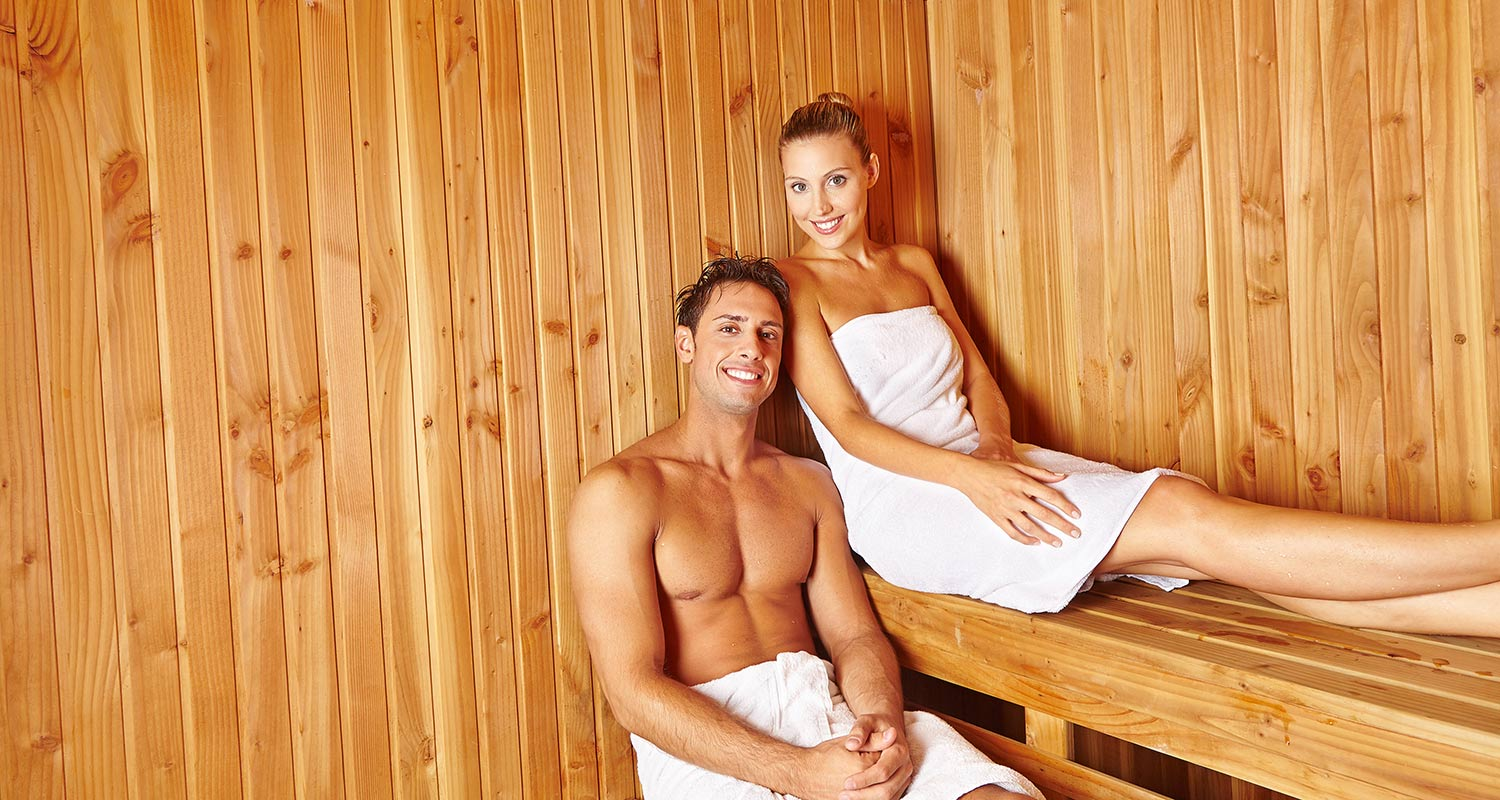 Couple with white towels in the Finnish sauna at Sporthotel Rasen