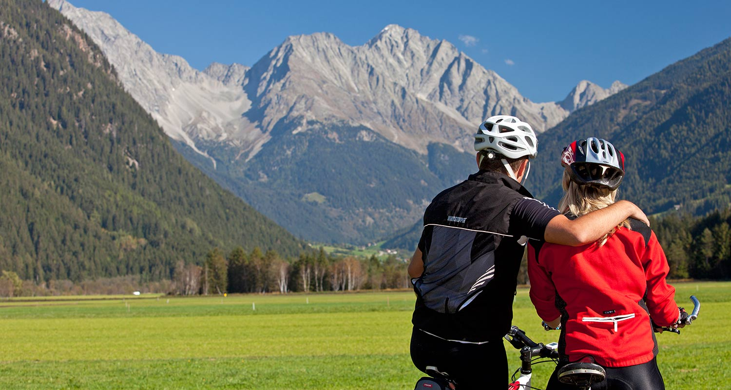 Cyclists having a break in front of a green mountain scenery