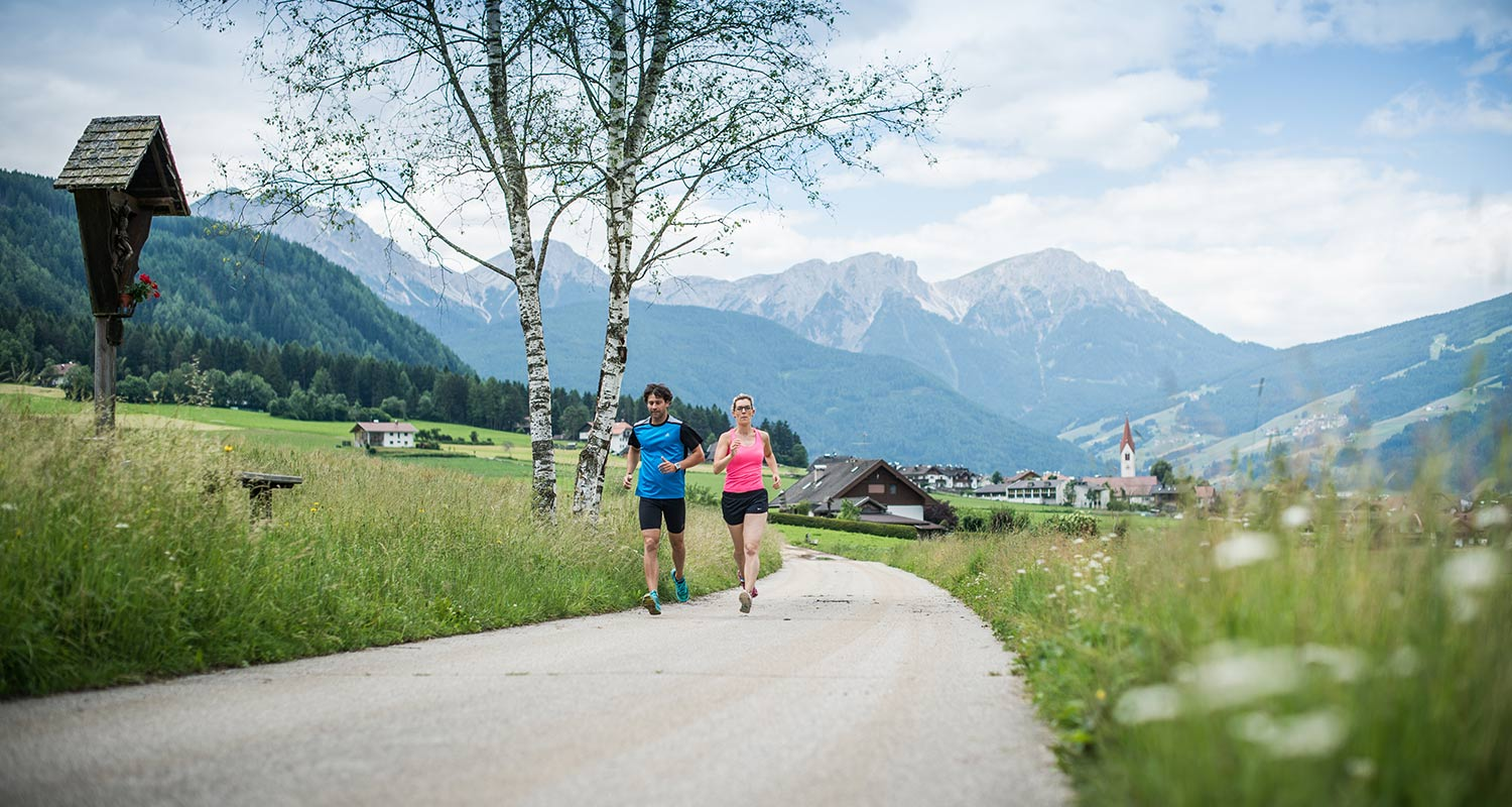 Couple jogging along a country road in summer