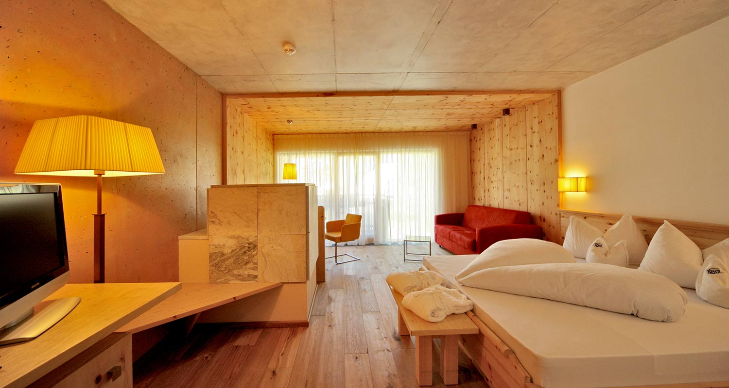 Bedroom with wooden furniture, double bed and balcony at Sporthotel Rasen