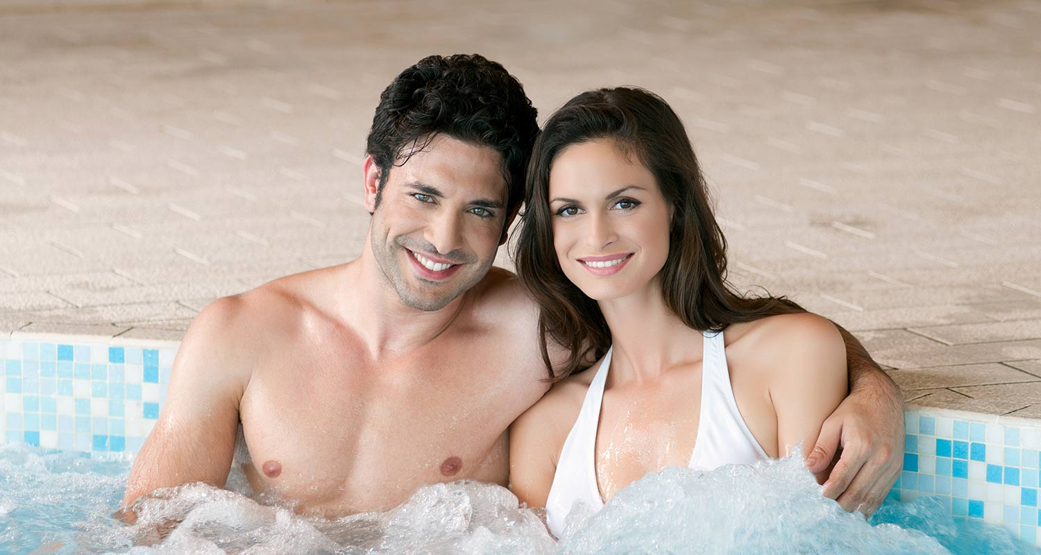 Smiling couple in the whirlpool of the wellness area at Sporthotel Rasen