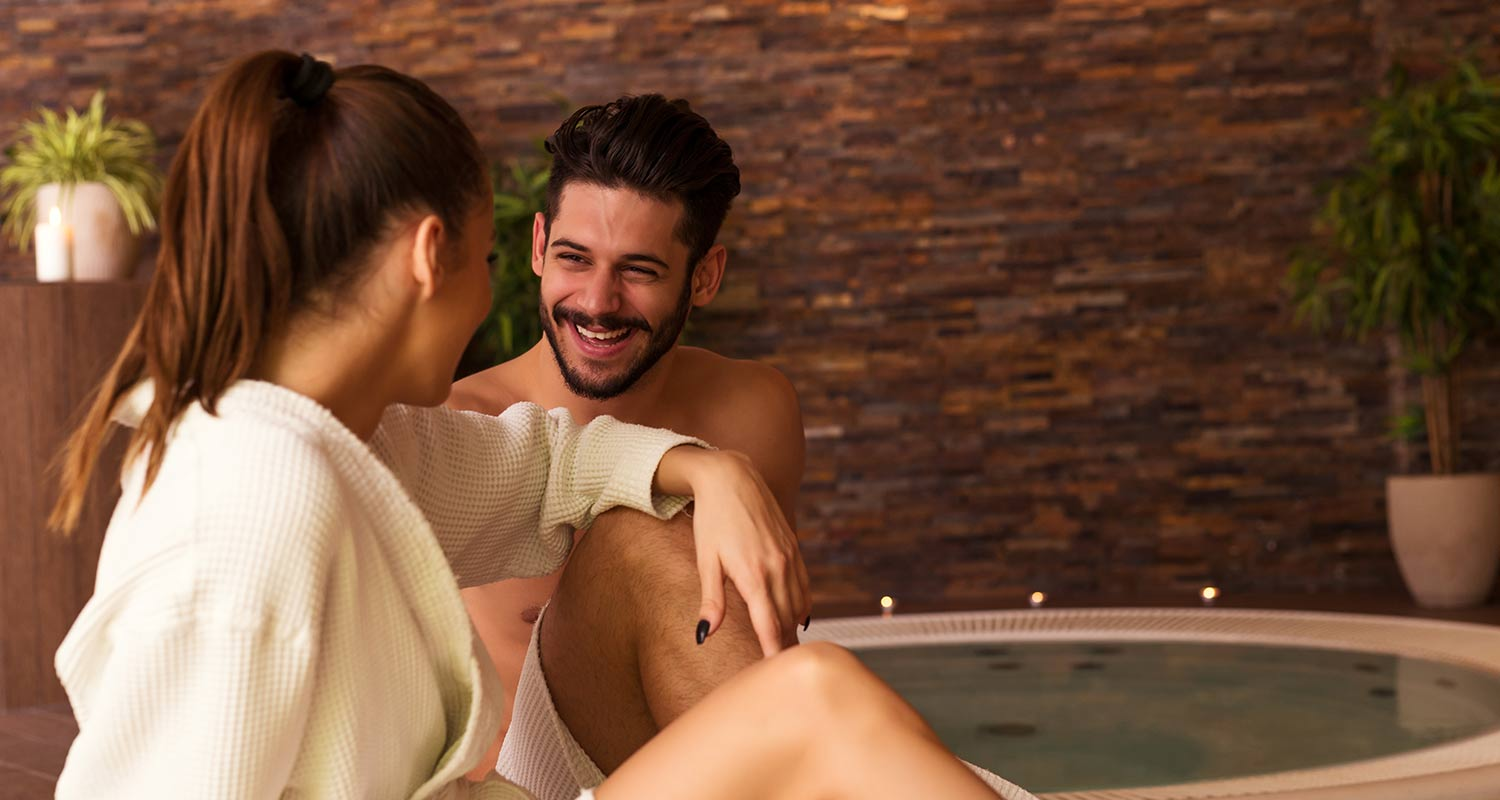 Couple smiling sitting at the whirlpool of Sporthotel Rasen