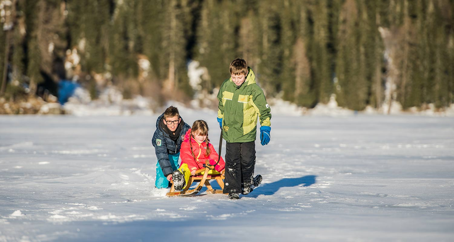 Children playing with toboggans on snowy surface
