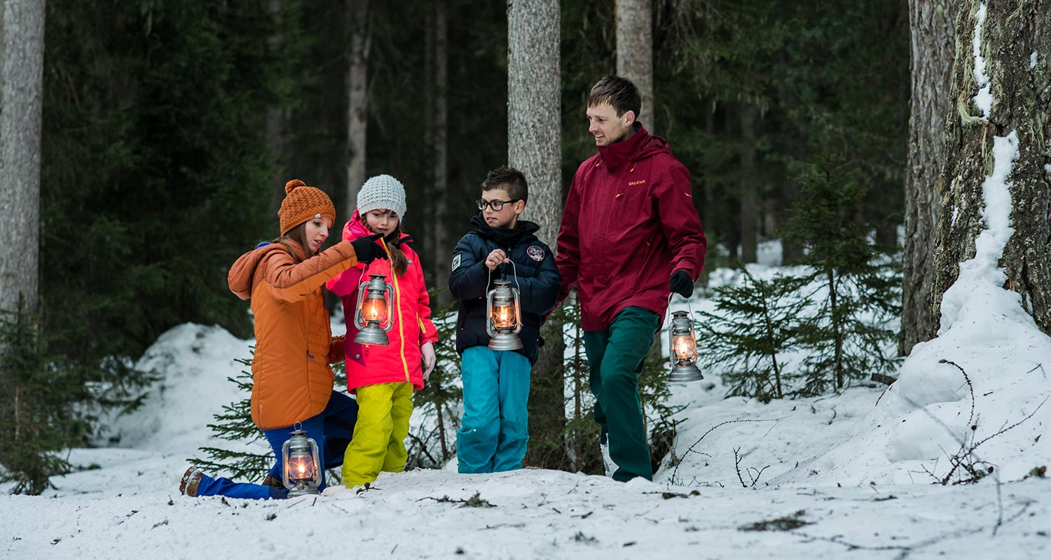 Children in winter clothes with lanterns in the snowy woods